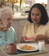 MFCU ElderSquad: Caregiver helping elderly woman with a meal.